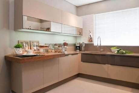 15. Decoração em tons neutros com armário de cozinha planejado com bancada de madeira – Foto: Hall Arquitetura