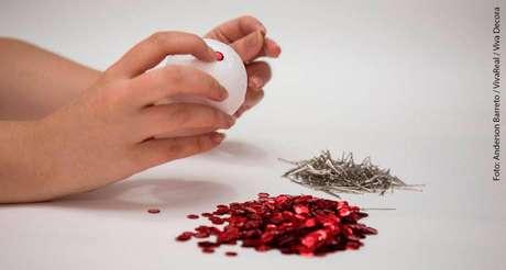 3.O primeiro passo de como fazer bolas de natal com lantejoulas é posicionar uma peça sobre a bola de isopor