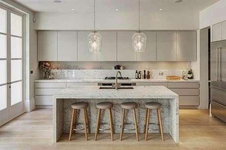 29. Cozinha com ilha decorada com armário de cozinha planejado cinza e pendentes de vidro sobre a ilha – Foto: Mujer Hoy