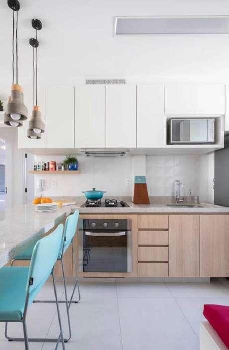 36. Cozinha decorada com cadeiras azuis, pendentes modernos e armário de cozinha planejado branco – Foto: Pinterest