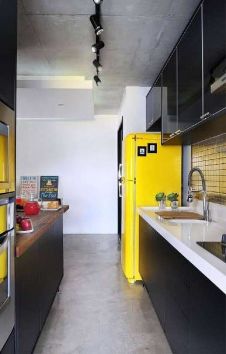 40. Modernidade para cozinha com armário de cozinha planejado preto e geladeira amarela – Foto: IBD Arquitetura