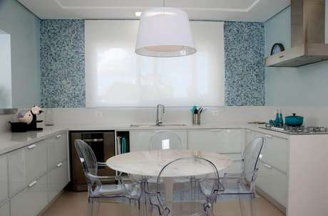 49. Decoração clean com armário de cozinha planejado branco e cadeiras de acrílico transparente – Foto: Juliana Pippi