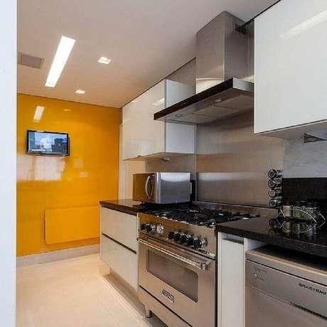 56. Decoração com armário de cozinha planejado branco e coifa inox – Foto: GF Projetos
