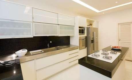 57. Decoração com armário de cozinha planejado branco e pastilhas pretas – Foto: Letícia Araujo