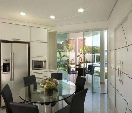 1. Cozinha planejada com armários brancos e mesa redonda de vidro – Foto: The Holk