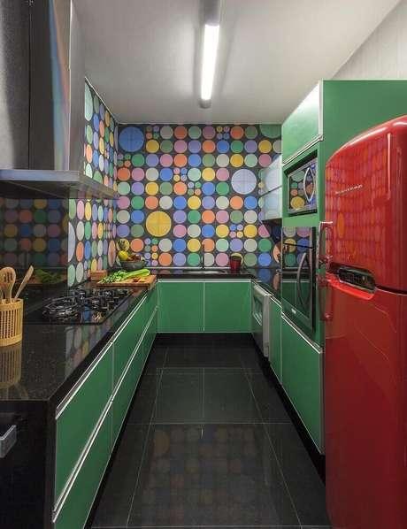 60. A parede com adesivo de bolinhas deixou o ambiente com armário de cozinha planejado em tom de verde ainda mais divertido – Foto: Nara Cunha