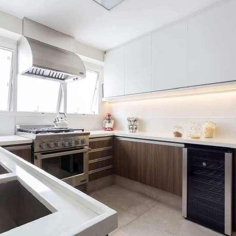 4. Decoração simples para cozinha com armário planejado branco e bancada de madeira – Foto: BMG Arquitetura