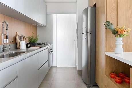 79. Os toques de madeira deixam o ambiente com armário de cozinha planejado mais aconchegante – Foto: Doob Arquitetura