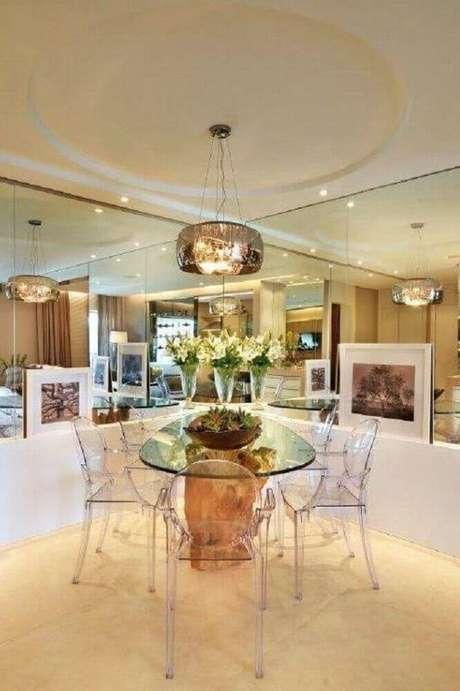 4 Decoração com cadeiras de acrílico transparente para sala de jantar moderna com paredes espelhadas e base da mesa com tampo de vidro feita em madeira – Foto: Quitete & Faria