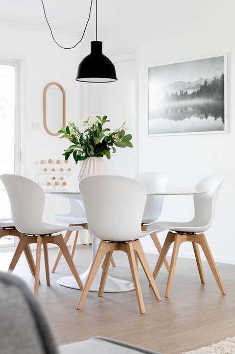 13. Decoração clean com cadeiras para sala de jantar moderna e pendente preto sobre a mesa – Foto: Pinterest