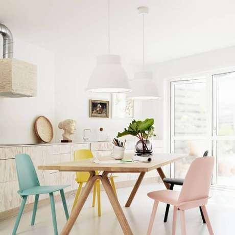 17. Decoração clean para sala de jantar com cadeiras coloridas em tom pastel e pendentes brancos sobre a mesa de madeira – Foto: Nicholas C Johnson