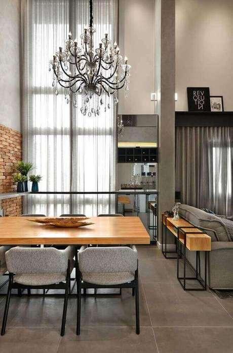 2. Vários elementos criam um espaço harmônico e uma decoração aconchegante para essa sala de jantar moderna e sofisticada com lustre e mesa de madeira – Foto: Evolukit