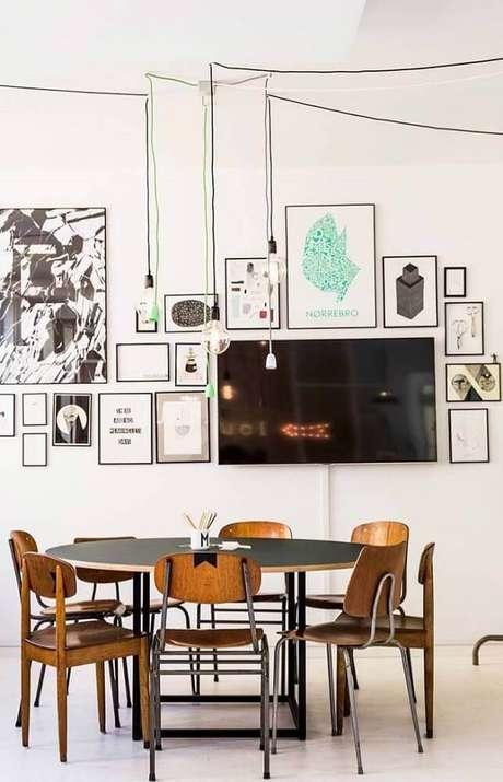 9. Decoração de sala de jantar moderna com pendentes minimalistas e muitos quadros na parede – Foto: The Holk