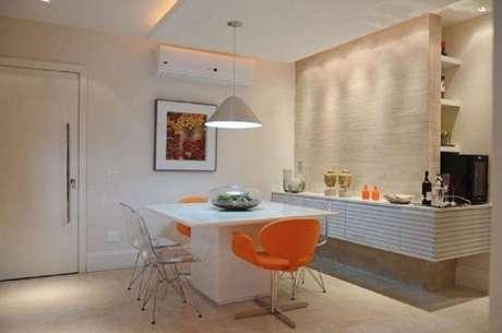 28. Decoração de sala de jantar moderna com cadeiras laranjas e transparentes – Foto: FPR Studio