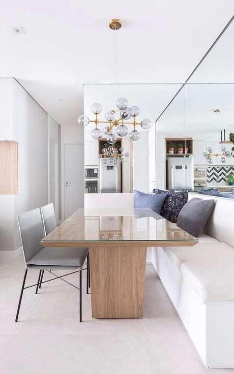29. Decoração de sala de jantar moderna com canto alemão, pendente minimalista e parede espelhada – Foto: The Holk
