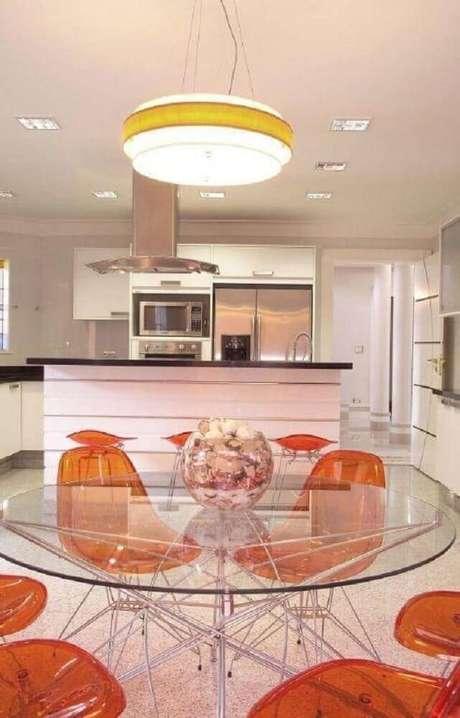 37. Decoração de sala de jantar moderna com mesa redonda de vidro e cadeiras plásticas laranjas – Foto: Aquiles Nicolas Kilaris
