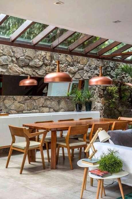 39. Modelo de pendente para sala de jantar moderna com parede revestida de pedra e mesa de madeira – Foto: The Holk