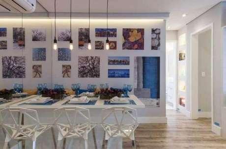 55. Modelo de cadeiras diferentes para sala de jantar moderna decorada com quadros e parede espelhada – Foto: Adriana Fontana