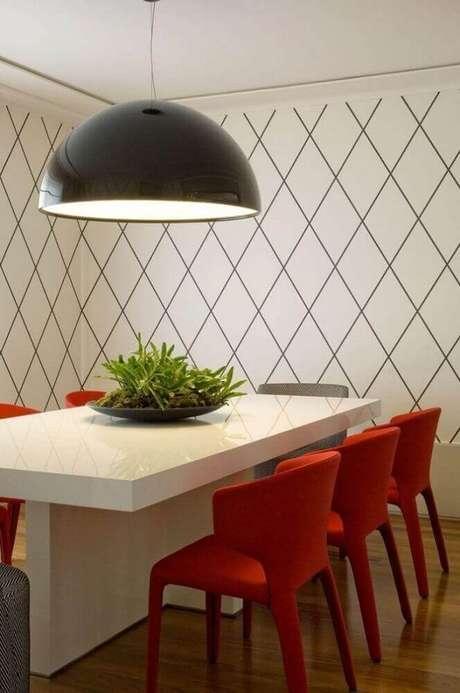 59. Sala de jantar moderna decorada com pendente preto e cadeiras vermelhas – Foto: Roberto Migotto