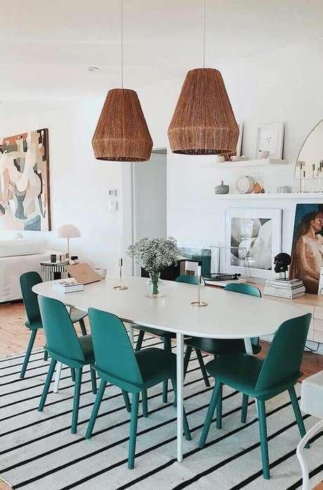 10. Decoração de sala de jantar moderna com tapete listrado e cadeiras verdes – Foto: Pinterest