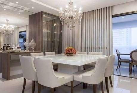 62. Decoração para sala de jantar moderna e sofisticada com parede espelhada e lustre candelabro sobre a mesa – Foto: Vanja Maia