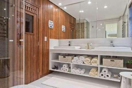 23. Banheiro planejado com nichos embaixo da bancada e grande espelho – Foto: Samara Barbosa