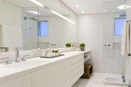 31. Os móveis planejados para banheiro podem receber pequenos objetos decorativos como vasos de flores – Foto: Triplex Arquitetura