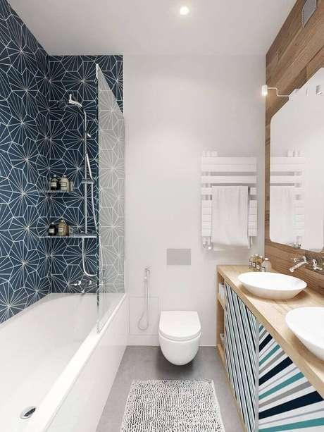 33. Decoração para banheiro pequeno planejado com azulejo estampado e armário planejado de banheiro em madeira – Foto: Construye Hogar