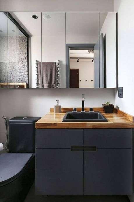 40. Decoração moderna com armário de banheiro planejado preto com bancada de madeira – Foto: Mandril Arquitetura e Design