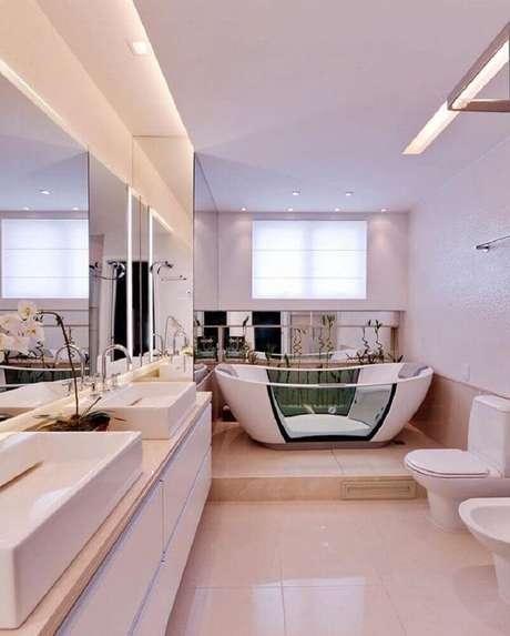 57. Decoração sofisticada para banheiro planejado moderno com duas cubas e banheira – Foto: Claudia Pimenta