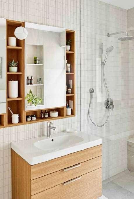 59. Decoração estilo escandinava com armário planejado para banheiro todo branco e com pequenos nichos em madeira ao redor do espelho – Foto: Pinterest