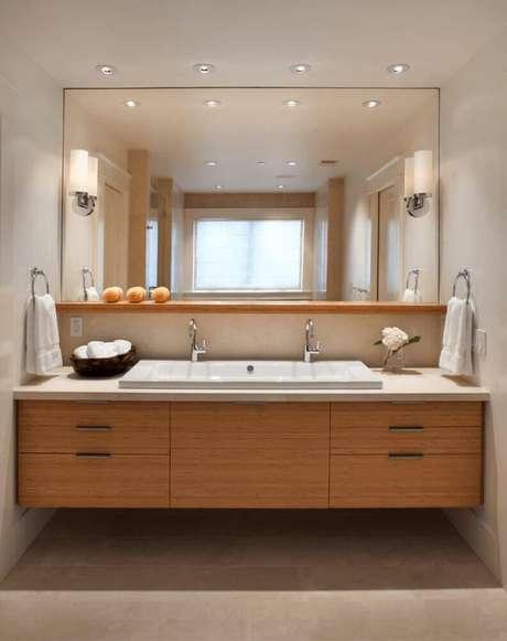 64. Decoração com armário de banheiro planejado com grande espelho e gabinete de madeira – Foto: Archilovers