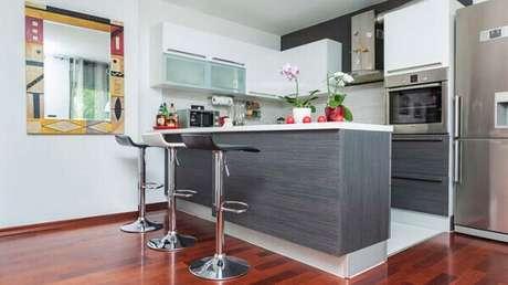 66- A cozinha americana simples foi decorada com revestimento de madeira na cor cinza nas portas dos armários e bancada. Fonte: Idea Brasil