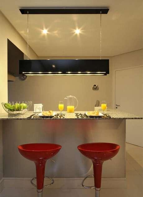 23- O conjunto de luminária retangular e bancada divide os ambientes entre a cozinha americana pequena e a sala de estar. Fonte: 3K Arquitetura e Interiores