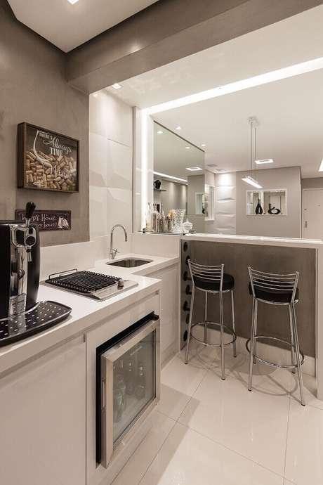 24- A cozinha americana simples tem pia em tamanho compacto e bancada utilizada como divisória. Fonte: Red Square Arquitetura