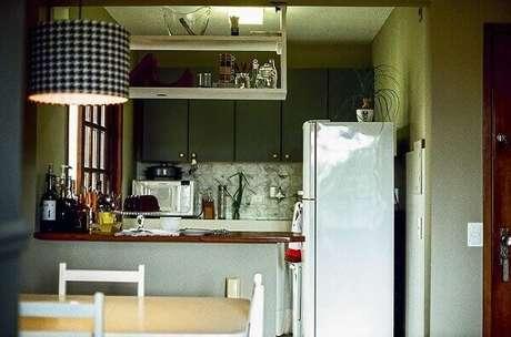 25- Na cozinha americana pequena foi construída uma mureta com tampo em madeira natural. Fonte: Casa Aberta