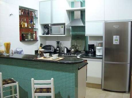 64- As pastilhas verdes revestem a bancada e a área do fogão na cozinha americana pequena. Fonte: This is the Crosby