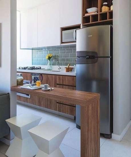 35- Cozinha americana pequena tem aparador vazado e banquetas baixas entre os ambientes. Fonte: Pinterest