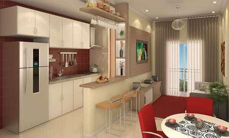 40- Na decoração de cozinha americana pequena com sala simples foi utilizada a mesma tonalidade de madeira da bancada e no painel. Fonte: Decorando Casas