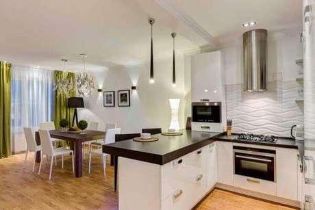 63- A cozinha americana pequena com acabamentos em branco e preto complementa a decoração da sala de estar. Fonte: Chaves na Mão