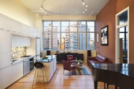 51- A bancada da cozinha americana pequena com sala tem uma estrutura elevada em vidro. Fonte: Tudo Construção