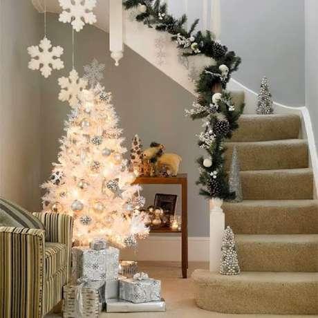 4. Linda decoração natalina com árvore branca bem iluminada e corrimão de escada com enfeites natalinos – Foto: Always in Trend