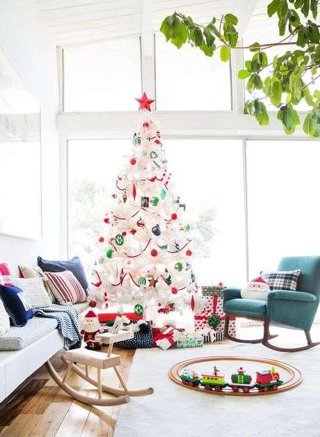 55. Linda decoração para sala bem clara com grande árvore de natal decorada com enfeites coloridos – Foto: Emily Henderson