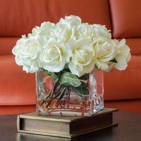 26- O vaso quadrado de vidro transparente tem arranjo de rosas artificiais na cor branca. Fonte: Casa e Festa