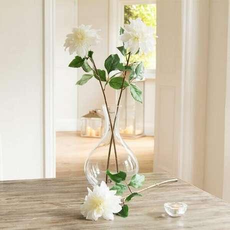 23- As três flores artificiais brancas em um vaso alto de vidro transparente cria uma atmosfera de leveza e requinte ao ambiente. Fonte: Peony