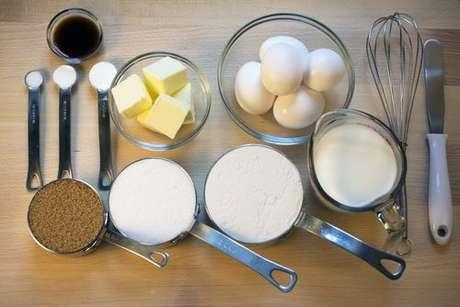 Colheres e xícaras medidoras e ingredientes para fazer um bolo