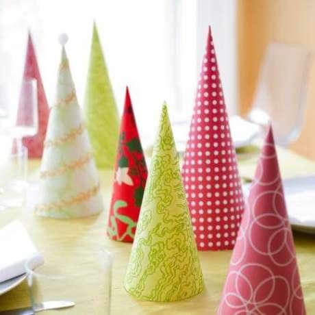 64. Outra opção de DIY é fazer cones de papel coloridos para fazer a decoração de mesa de ceia de natal. Foto de Midwest Living
