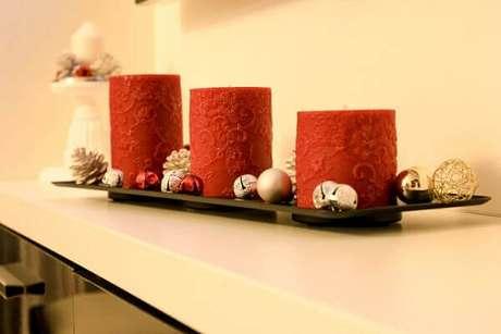 8- Decoração de natal simples e barata com velas vermelhas de tamanhos diferentes. Fonte: Lucian Andrei