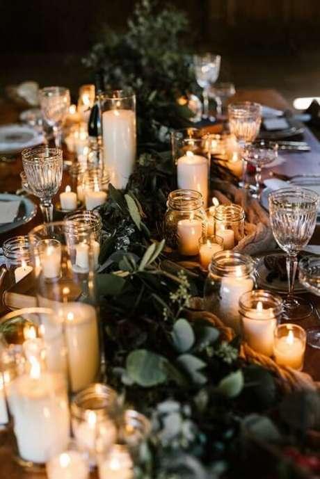 32. Mesa com várias velas e ramos de árvores no centro. Foto de 100 Layer Cake