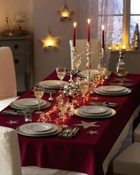 66. Toalha de mesa vinho com candelabro dourado e pisca pisca sobre a mesa da ceia de natal. Foto de North Mallow